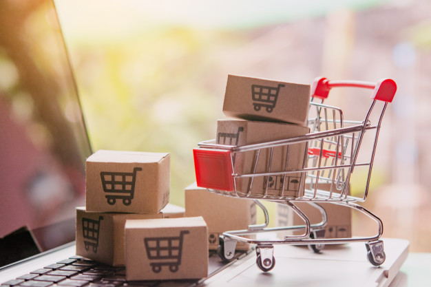 shopping-online-concept-parcel-paper-cartons-with-shopping-cart-logo-trolley-laptop-keyboard-shopping-service-online-web-offers-home-delivery_9635-3259